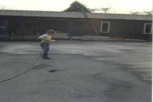 Employee spraying sealer on a parking lot